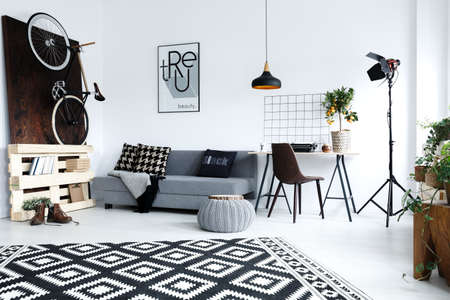 Modern, white apartment with grey sofa, desk, chair, lamp, carpet