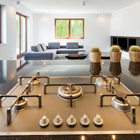 ascetic: Modern kitchens gas cooktop, with spacious living room in the background