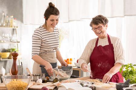 Happy grandma and granddaughter preparing dinner together