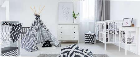 Ruime zwart-witte babykamer ontworpen in Scandinavische stijl Stockfoto