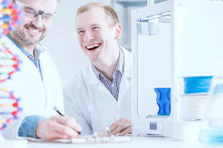 smiled: Smiled scientists at work with 3D printer in laboratory