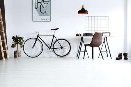 open floor plan: Simple, white room with bike, desk, chair, lamp, ladder, poster