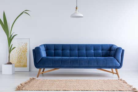 白いシンプルなリビング ルームでブルーのソファ、籐カーペット
