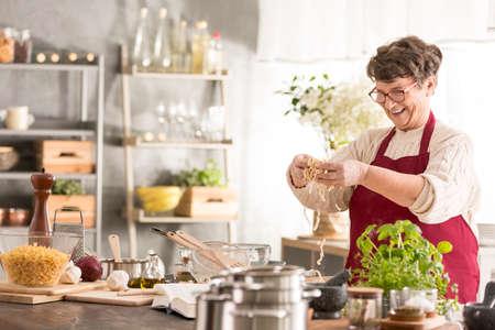utensilios de cocina: Feliz mujer mayor cocina en su cocina moderna
