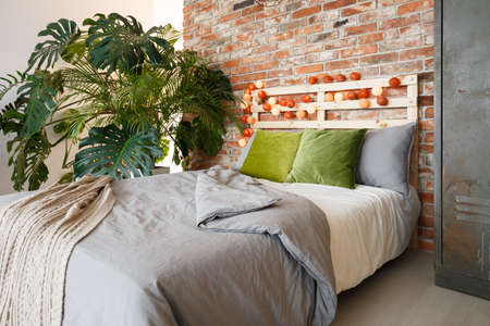 Modern bedroom with brick wall, king-size bed and monstera