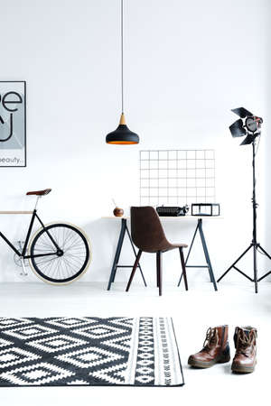 open floor plan: Modern black and white room with bike, desk and lamp Stock Photo