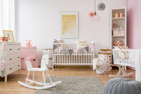 Baby room in stile scandinavo con cavallo a dondolo, lettino bianco Archivio Fotografico - 77583486