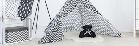 White and black room with tipi tent and teddy bear prepared for kids