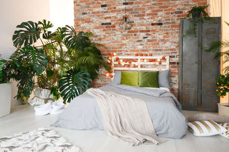 King-size bed, metal locker and monstera in modern bedroom with brick wall