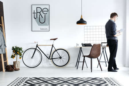 Modern, white home interior with desk, chair, bike, poster Stock Photo - 78102322