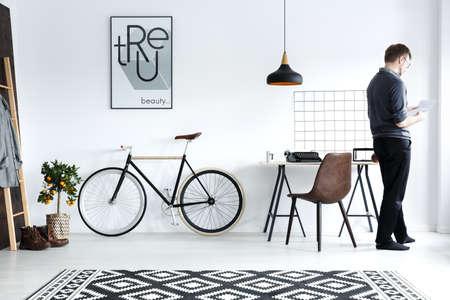 Modern, white home interior with desk, chair, bike, poster Stockfoto