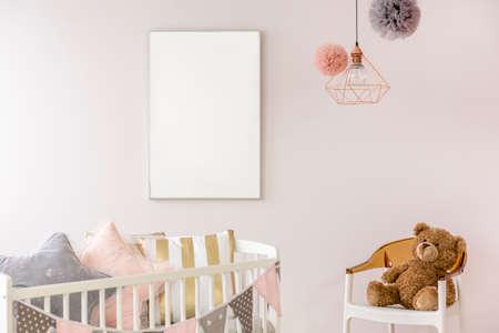 Newborn bedroom with white crib, chair, copper lamp, teddy bear Stock Photo
