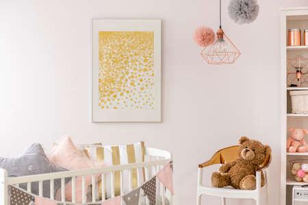 Kleuter slaapkamer met witte wieg, poster, stoel en teddybeer Stockfoto