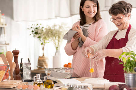 Happy grandma cracking an egg and cooking in a kitchen with her granddaughter