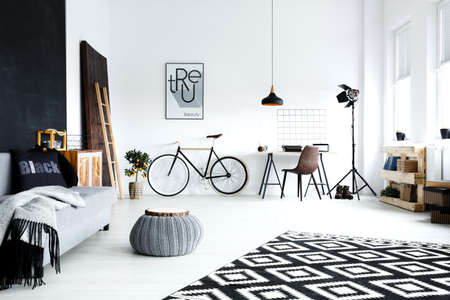 Open plan, white studio flat with sofa, bike, pouf, desk