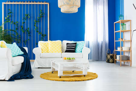White and blue spacious living room with yellow additions Stock Photo