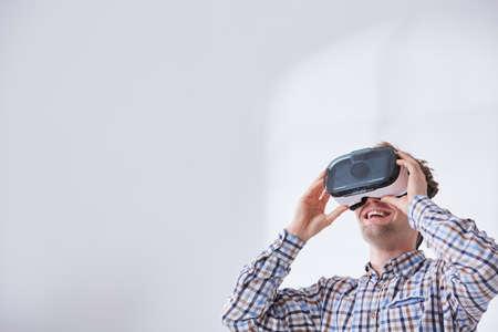 Hombre feliz con gafas de realidad virtual, fondo blanco Foto de archivo - 78075033