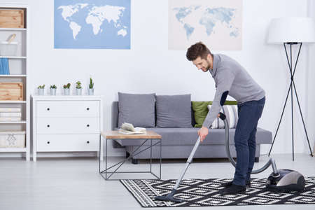 pedant: Smiling young man vacuuming in his living room