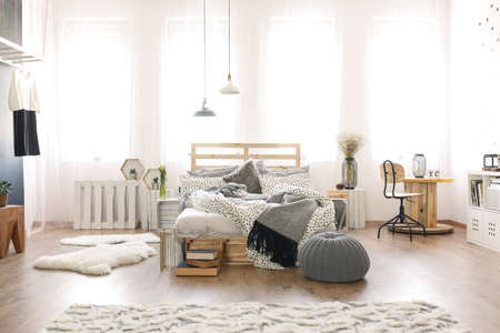 Modern spacious bedroom with wooden furniture Фото со стока