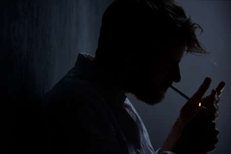 Depressed man smoking cigarette in the dark room Stock Photo