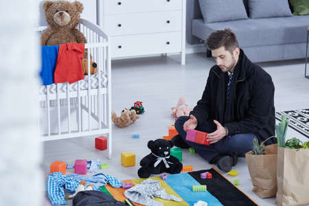 Sad young man sitting on a floor in nursery and playing with toys Stok Fotoğraf