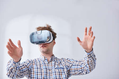 Man using modern vr goggles, white background Stock Photo
