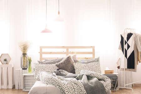 Wit en grijs slaapkamer interieur met kingsize bed en vrouwenkleren Stockfoto
