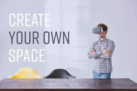 Creative businessman wearing modern vr goggles, standing beside desk