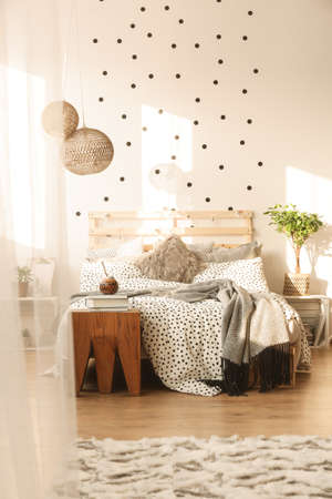 King-size bed with trendy bedroom with dots on the wall