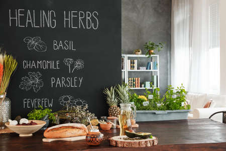Wooden dining table with healthy food and herbs