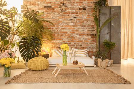 Gezellige botanische stijl woonkamer met bank en grote planten Stockfoto