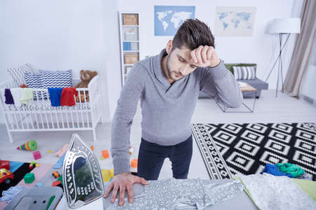 Tired young man ironing childs clothes in messy nursery