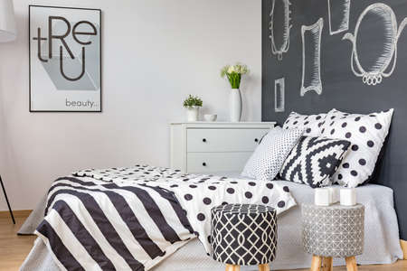 stool: Black and white bedding on comfortable bed in modern bedroom