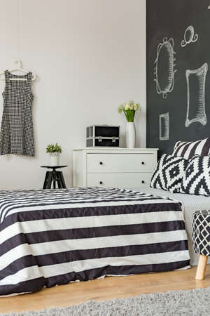 stool: Female bedroom in black and white with bed and trendy blackboard wall