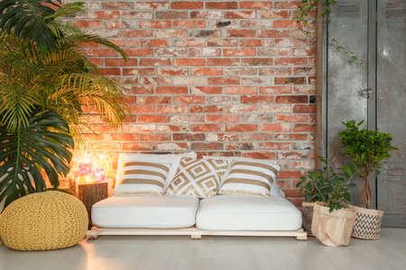 White sofa made of wooden pallets in cozy living room