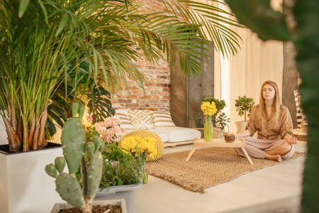 Girl meditating in cozy botanic style room full of plants