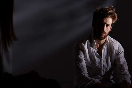 Depressed and thoughtful man sitting alone in dark room