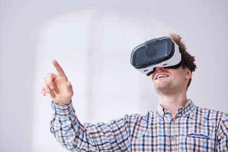 Hombre feliz con casco de realidad virtual, fondo blanco Foto de archivo - 78013222