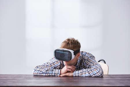 Hombre joven con gafas vr, sentado al lado del escritorio vacío Foto de archivo - 78104569