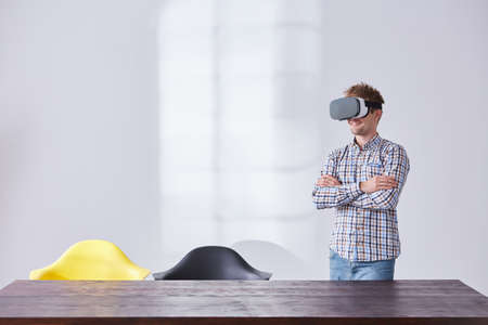 Hombre con el receptor de cabeza de la realidad virtual que se coloca en la oficina brillante Foto de archivo - 78104573