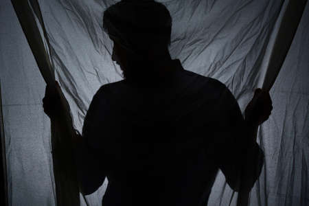 Shadow of a man standing behind the drape