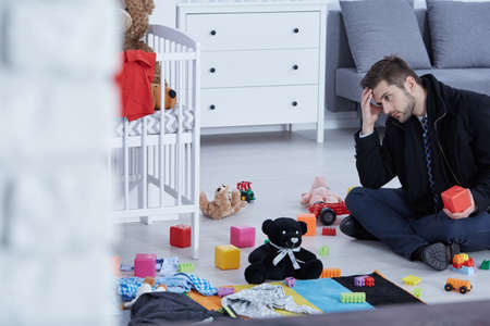 Tired young dad sitting on a floor full of children toys