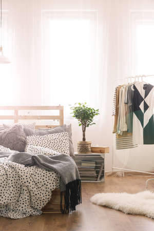 King-size bed and womans clothes in modern bedroom