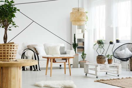 Wooden and white furniture in cozy living room in scandi style