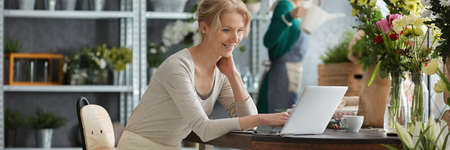 Young blonde woman with laptop and flowers on the desk