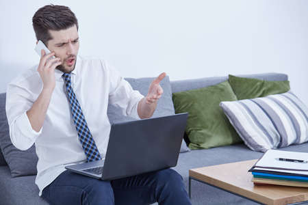 Outraged young businessman talking on the phone and looking at his laptop at home