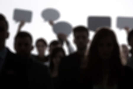 Blurred crowd of people holding speech bubbles above their heads