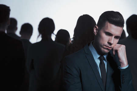 Sad young businessman in a suit standing against an anonymous crowd