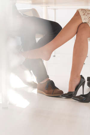 lustful: Woman provocatively touching mans leg under the table at the office