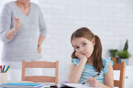 Girl sitting at the desk but unwilling to do homework Stock Photo